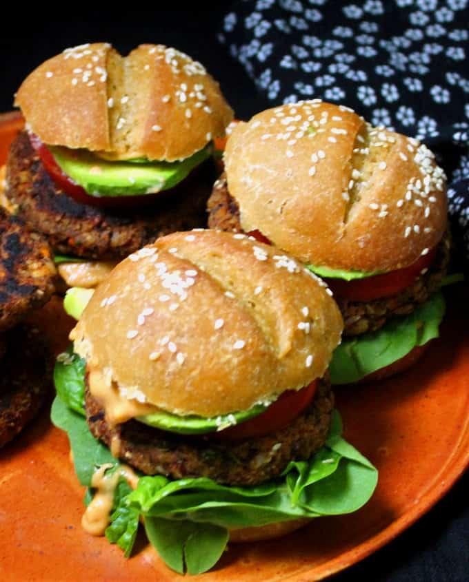 Front closeup of three vegan black bean burgers with greens and veggies.