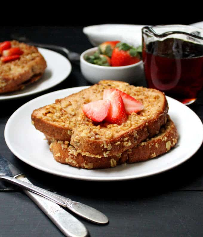A front shot of a plate of vegan French toast with fresh strawberries and maple syrup.