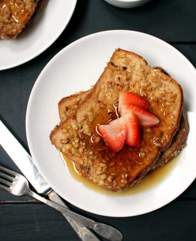 A closeup of a plate of vegan French Toast topped with strawberries and maple syrup in a white plate, on a black table with a knife and fork.