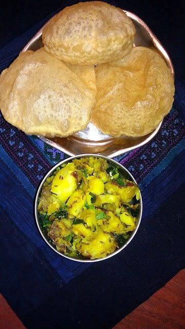 A bowl of batata bhaji with pooris nex to it.