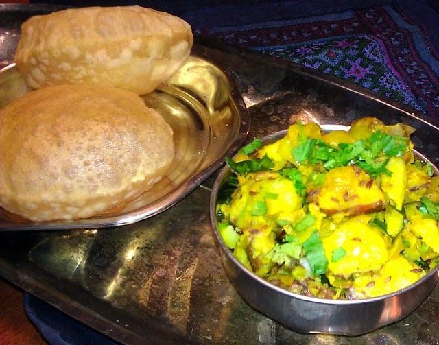 A tray with batata or aloo sabzi and puffy pooris.