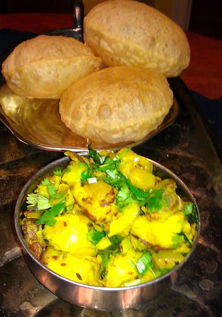 A bowl of batata or potato sabzi with pooris in the background.