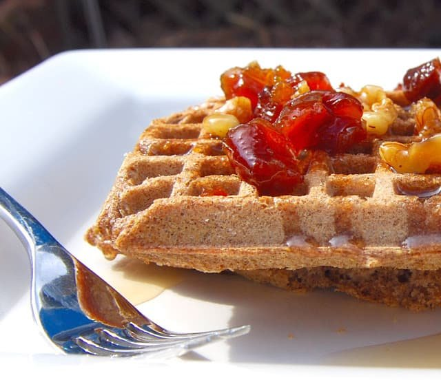 Photo of two vegan gluten-free waffles with buckwheat and brown rice served with a fruit and nut syrup on a white plate with fork.