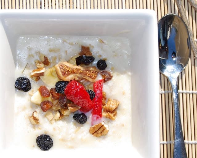 Photo of a bowl of oatmeal with fruits and nuts.