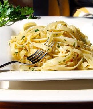 Fettucine aglio de olio in a plate with a fork.