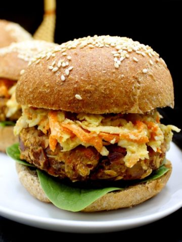 Front photo of a vegan bean and oats veggie burger on a whole wheat burger bun with cole slaw and greens