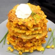 A stack of vegan corn fritters with chives and cream cheese on a gray plate