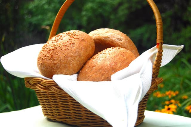 Whole wheat buns in a wicker basket in the outdoors.