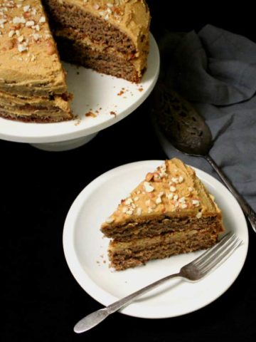 A top shot of a slice of vegan banana cake with peanut butter frosting on a white plate with a fork and the full cake on a cake stand in the back