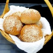 Whole wheat hamburger buns in a straw basket nestled in cheesecloth
