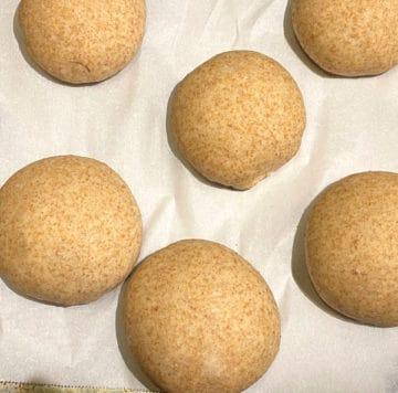 Burger buns rising on baking sheet