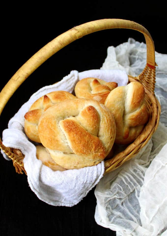 Overhead front shot of a basket with golden, fresh-baked homemade sourdough pretzels in a wicker basket and nestled in a white napkin witha  cheesecloth next to it.