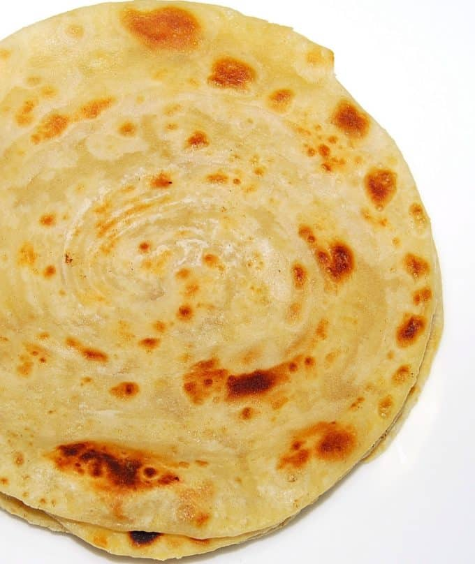A partial shot of flaky, crispy, multi-layered khasta parathas on a white background