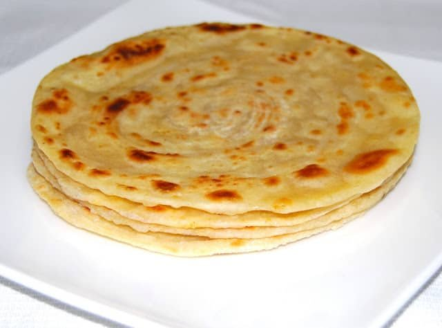 A stack of golden, freshly baked parathas on a white plate