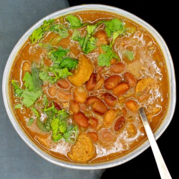 Vegan feijoada in a bowl with beans, sausage and cilantro.