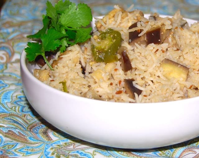 Front shot of a bowl of eggplant pulao with cilantro on a blue and green paisley tablecloth.