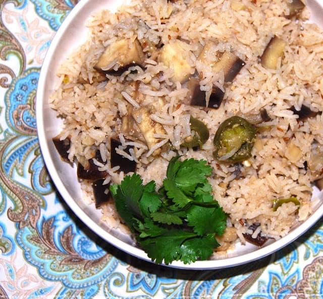 Photo of a bowl of eggplant pulao with cilantro garnish.