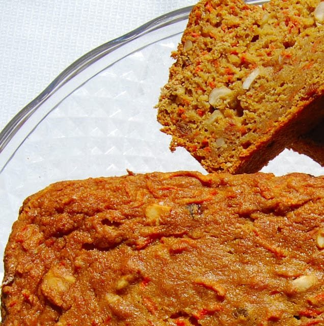 Vegan carrot bread loaf with a slice next to it on a glass cake stand.