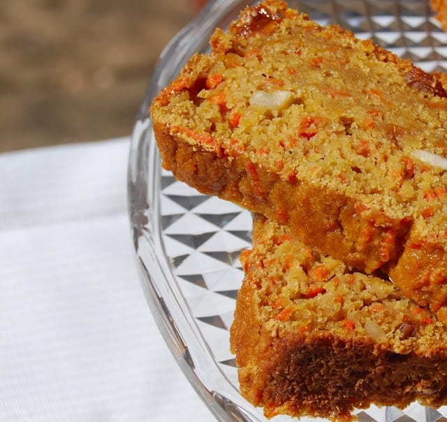 Two vegan carrot bread slices overlapping each other on a crystal cake stand.