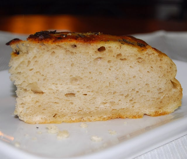 Photo of a slice of focaccia bread showing large, airy holes.