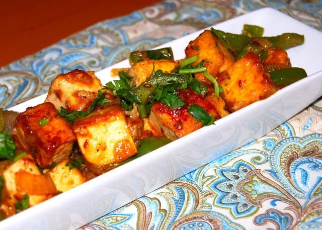 Indo Chinese style Chili tofu in a white, long, rectangle bowl