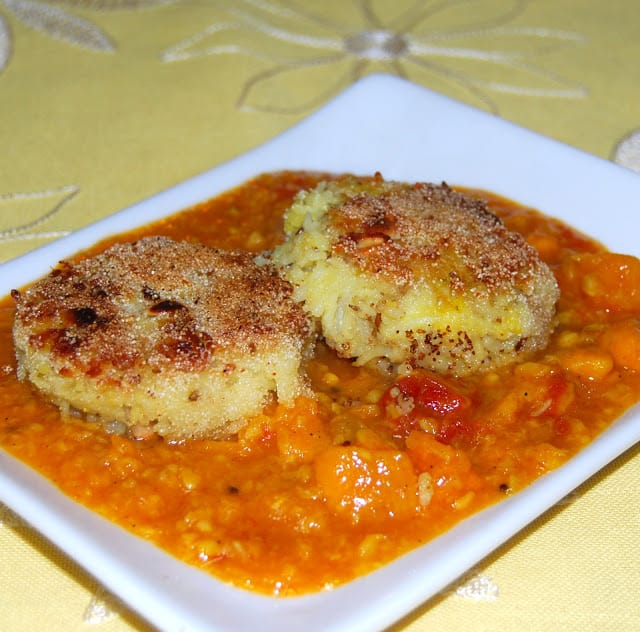 Photo of two crispy pongal cakes in sweet potato gotsu dal on a white plate.
