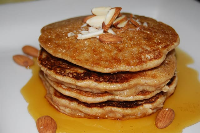 Picture of stack of vegan almond pancakes with maple syrup and chopped almonds.