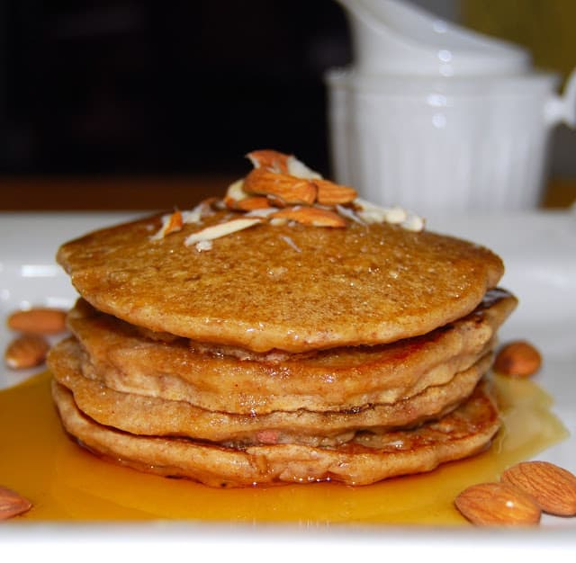 Photo of vegan almond pancakes with maple syrup and chopped almonds.