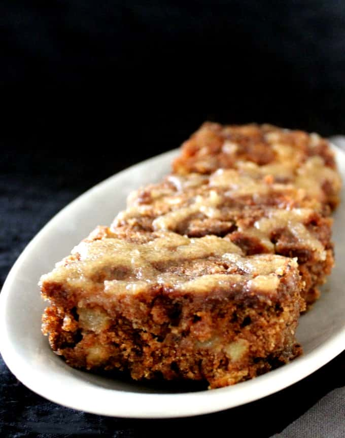 A front shot of three slices of vegan apple cake on a gray plate