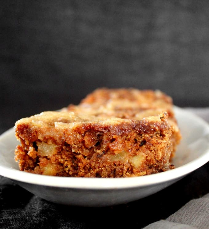 A cross section of a slice of vegan apple cake on a white plate with a black background