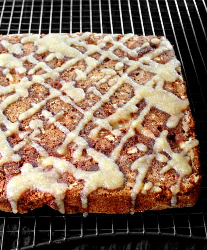 A front partial shot of a vegan apple cake with applesauce glaze on a black rack
