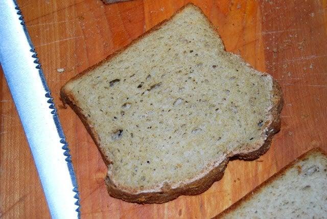 A slice of vegan gluten-free sandwich bread on chopping board with knife.