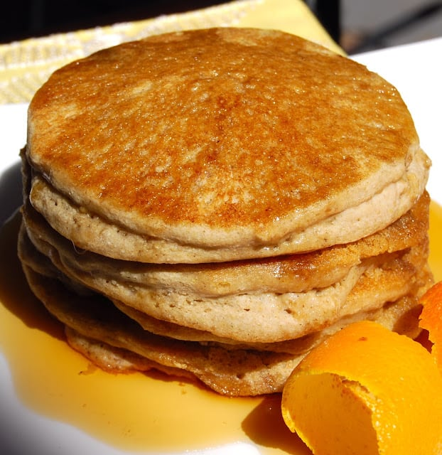 Photo of stack of four vegan glutenfree pancakes with maple syrup and orange peel.