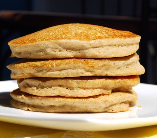 A front shot of four vegan gf pancakes stacked on a white plate.
