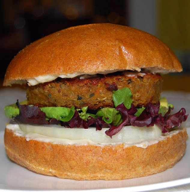Photo of quinoa and bean burger in a whole wheat burger bun with greens.