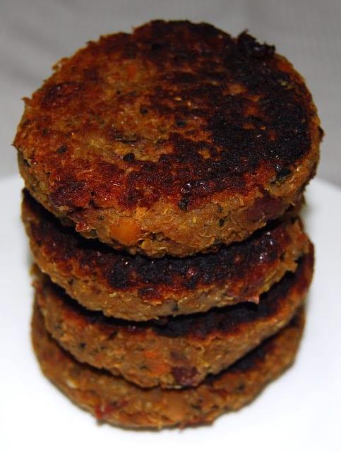 Four quinoa bean burger patties stacked.