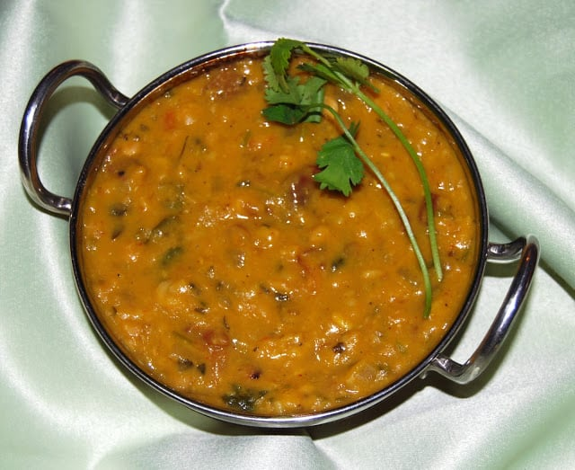 A kadhai with yellow dhabewali dal garnished with cilantro.