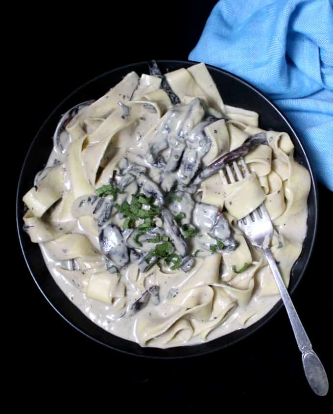 Overhead shot of Vegan Alfredo Sauce with Mushrooms and Cashews in a saucepan with a fork and a blue napkin beside it.