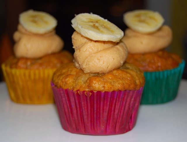 Photo of a vegan banana cupcake with peanut butter frosting and a slice of banana.