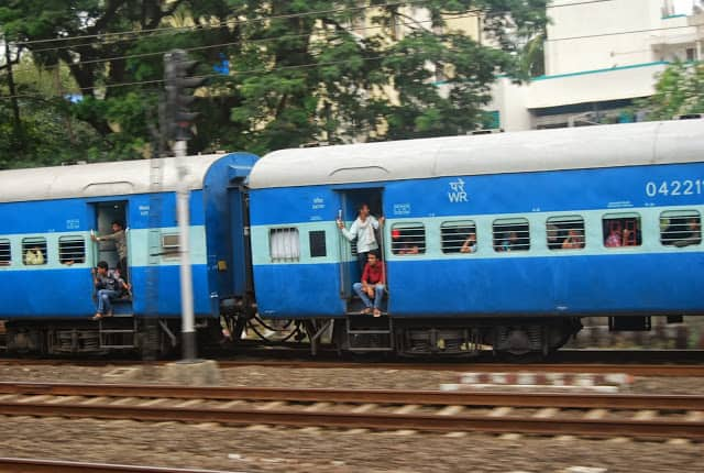 A blue and white long-distance train rides alongside the local train.