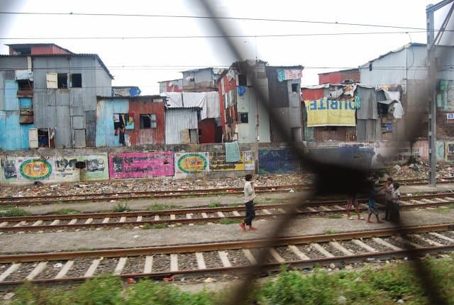 Children play alongside trains thundering on the tracks.
