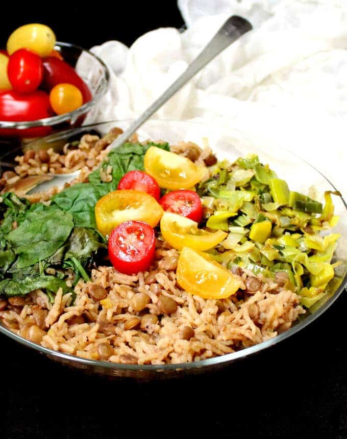 Vegan One Pot Mujadara with rice, lentils and greens served with greens and tomatoes in a glass bowl with silver spoon.