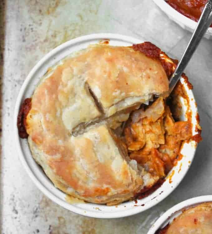 A close-up top shot of a golden, flaky chicken tikka masala pot pie with the tikka masala filling showing and a spoon
