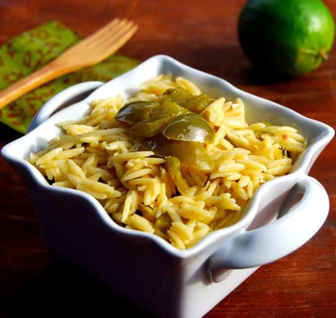 Lime Orzo in a square white bowl with a lime in background.