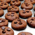 Vegan Death by Chocolate Cookies on a cookie sheet with chocolate chips