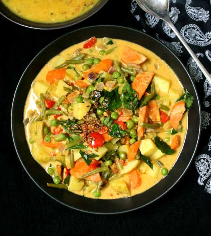 A bowl filled with vegetable korma, made with carrots, potatoes, green beans and tomatoes in a spicy but creamy coconut sauce. Next to the bowl is a paisley napkin and a bowl of dal and spoon.