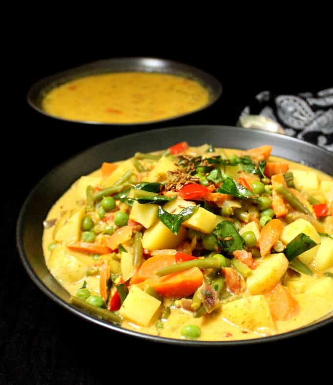 A front shot of a bowl filled with vegetable korma, made with carrots, potatoes, green beans and tomatoes in a spicy but creamy coconut sauce. Next to the bowl is a paisley napkin and a bowl of dal and spoon.