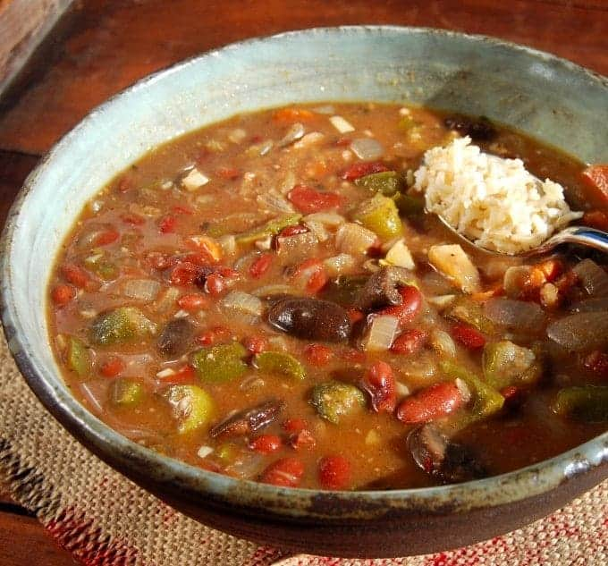 Front partial shot of a large bowl of vegan gumbo that's also gluten-free and fat-free, with a spoonful of brown rice, on a brown wood background.