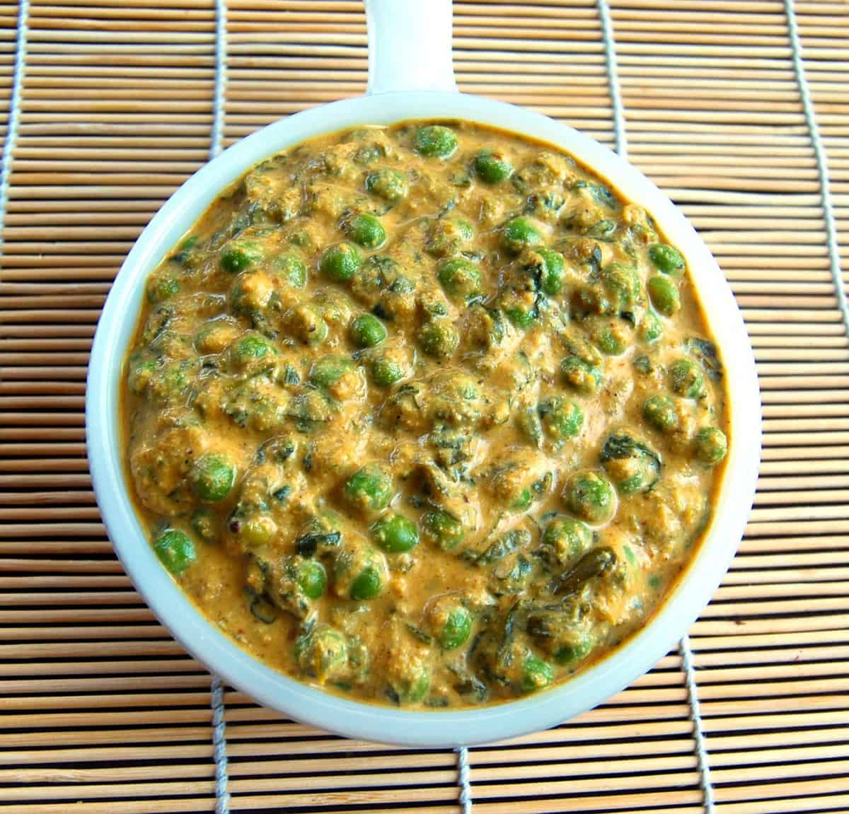 Overhead photo of methi matar malai or fenugreek and peas in a cream sauce in a white bowl on a straw mat.