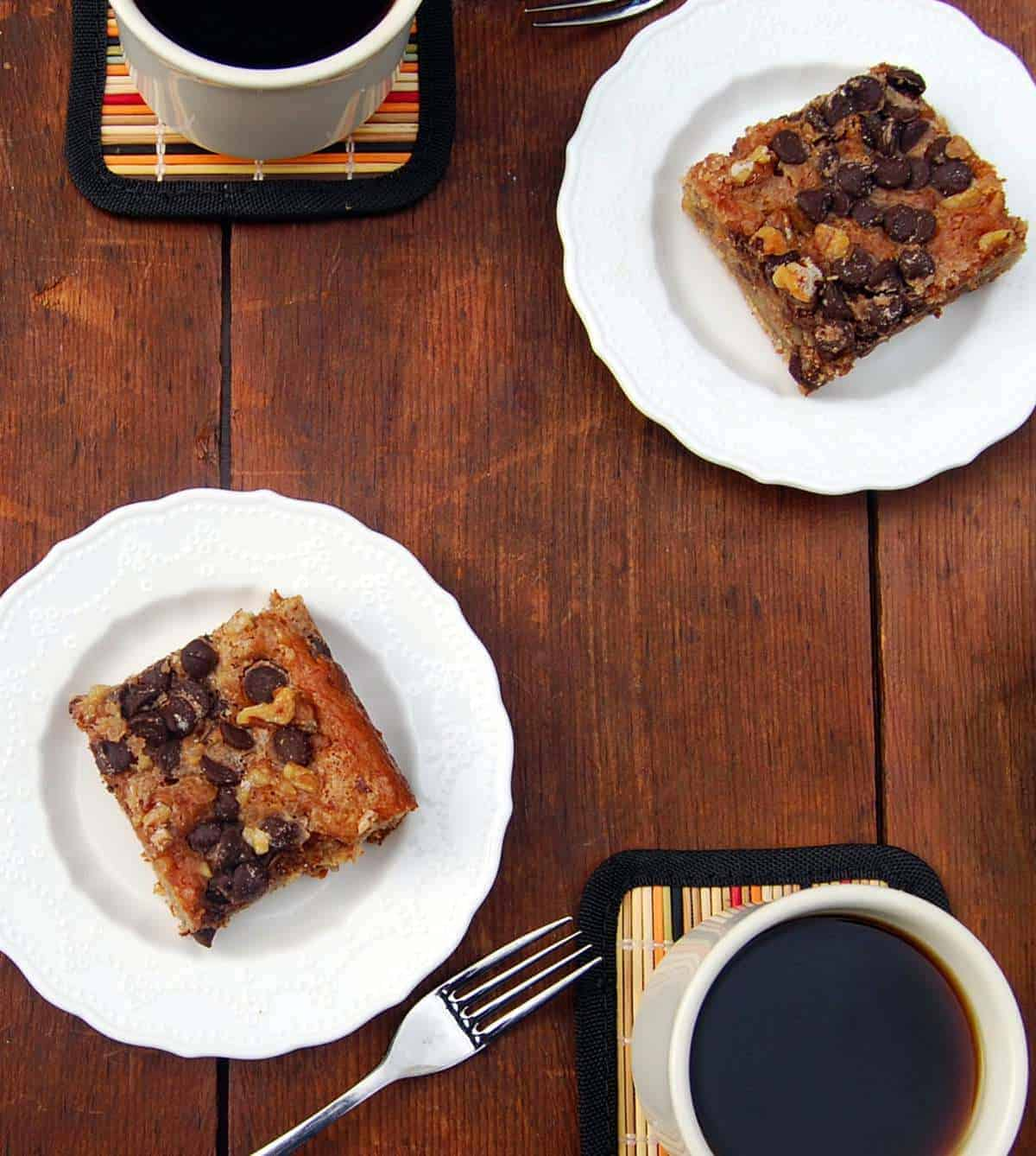 Vegan Banana Coffee Cake squares served on white plates with coffee.